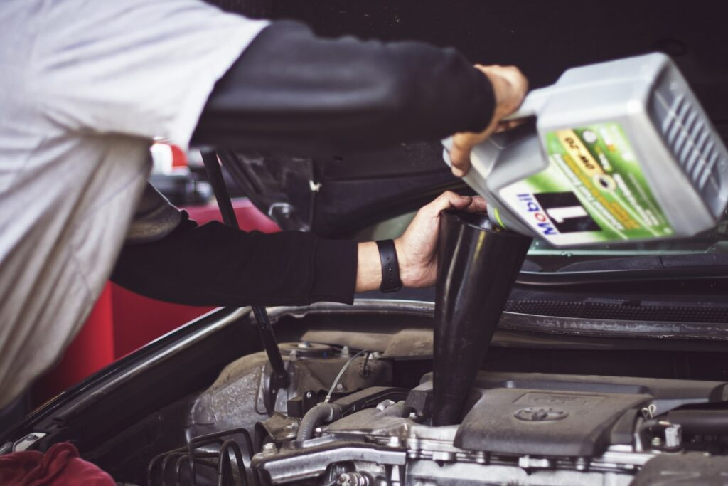 Mechanic holding an engine oil pouring on a car